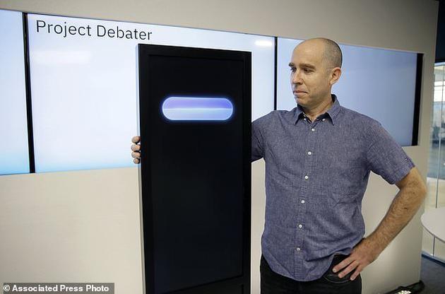 图为首席研究员诺姆•斯洛尼姆站在人工智能机器Project Debater旁边。该机器即将在接下来于旧金山展开的辩论赛中与两名人类对决。斯洛尼姆在程序中加入了幽默元素,但机器有时会在不合适的时机开玩笑。